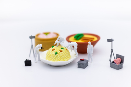 Miniature People and food, check the nutritional value, nutrients received in each meal. Image use for food and beverage concept. Stock Photo