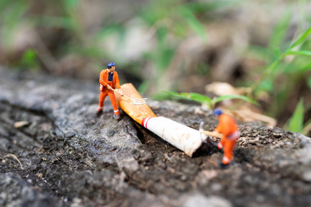 Miniature people: Worker are destroying cigarettes which is air pollution not safe for people. Use image for health concept.