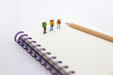 Miniature people: travelers standing on the book, traveling to destination. Use image for travel business concept.