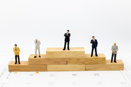 Miniature people : Businessmen standing in various positions of wooden , indicating the sequence of work, used as a business concept.
