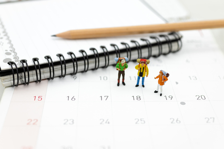 Miniature people, travelers standing on the calendar, mark date for traveling to destination. Used in the travel business concept. Stock Photo