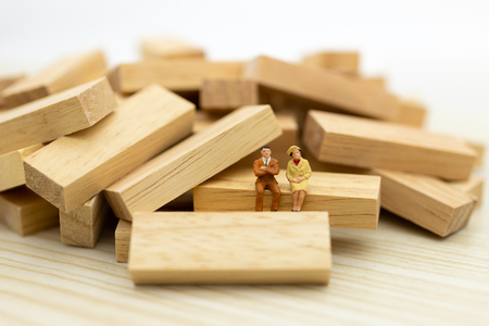 Miniature people : Businessman sitting on wooden , image use for business concept. Stock Photo