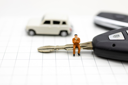 Miniature people : Businessman sitting on car key. Image use for Advertising product in the market today, competition on the business trading.