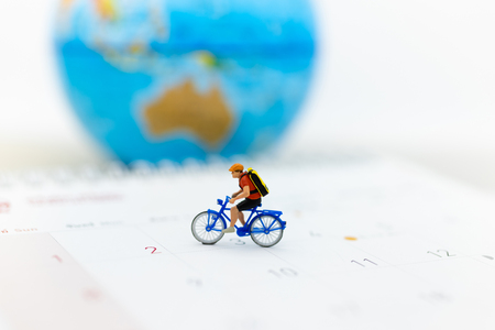 Miniature people : Travelers riding bicycle around the world. Image use for background traveling , business concep. Stock Photo