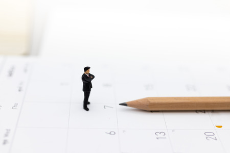 Miniature people : Businessman standing on the calendar to set the date for the meeting . Image use for business meetings concept.