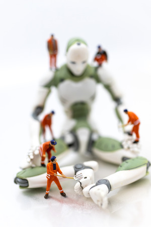 Miniature people : Engineering is developing an AI robot system, using labor instead of people. Image use for new technology in the feature, business concept.