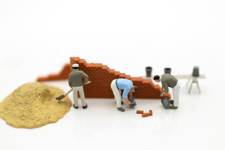 Miniature people: Construction workers building plans , have building materials, sand, brick, mortar. Use image for construction business.
