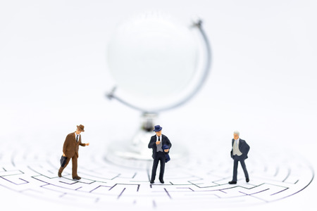 Miniature people : Businessmen standing on maze map and looking for a solution with teamwork. Image use for solve problems and new idea concept.