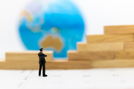 Miniature people: Businessman standing front of the wall and the world is inside. Image use for business security center, protect concept. Stock Photo