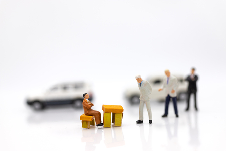 Miniature people: Businessman standing with white car.  Work and save money to buy a car. Image use for saving money from work to buy something you want.