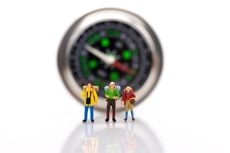 Miniature people : Traveler stand front the compass to tell the direction of travel. Image use for business travel concept.