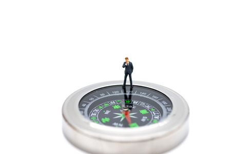 Miniature people : businessman standing with compass. Image use for business concept.