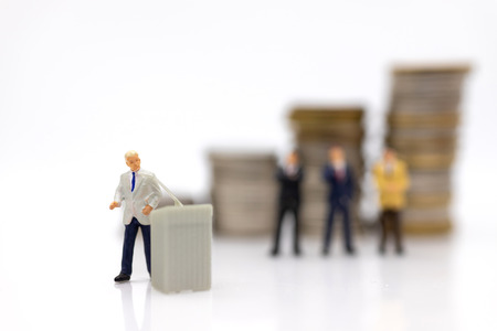 Miniature people:  Businessman standing on the stack of coins. Image use for business concept. Stok Fotoğraf