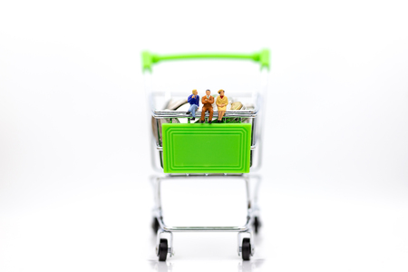 Miniature people : Businessman sitting on shopping cart on stack of coin. Image use for retail business concept. Stok Fotoğraf