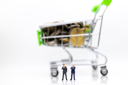 Miniature people : Businessman standing with shopping cart on stack of coin. Image use for retail business concept.