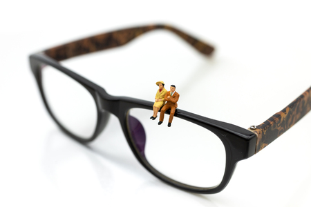 Miniature people : Businessman sitting on a glasses. Image use for business concept.