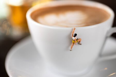 Miniature people : Coffee cup , image use for charge your energy in the morning