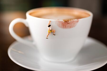 Miniature people : Coffee cup with lipstick marks image use for charge your energy in the morning Stock Photo