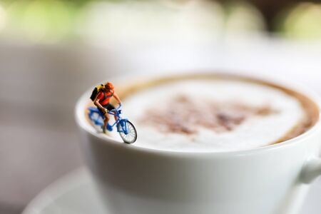 Miniature people : Coffee cup with cycling, image use for charge your energy in the morning Stock Photo