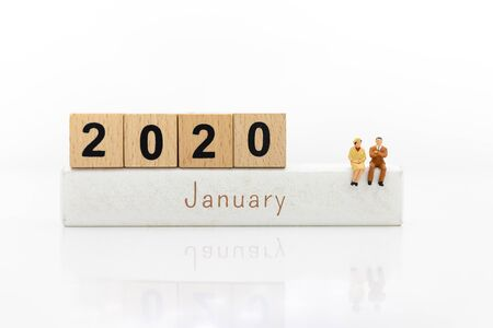 Miniature people: Businessman sitting on wooden block 2020. Image use for beginning new thing, business concept.