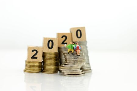 Miniature people, Old couple figure sitting on top of stack coins using as background retirement planning, Life insurance concept. Stock Photo