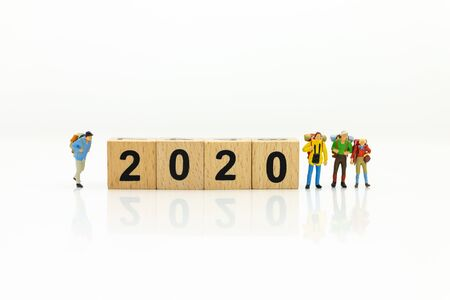 Miniature people, group travelers standing on wooden block 2020, new year. Image use for travel business concept.