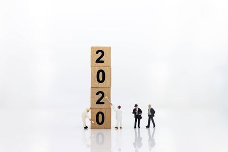 Miniature people : Businessman with wooden block new year, Image use for the new beginning of life, business concept