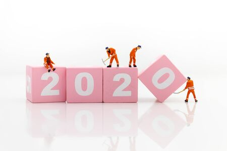 Miniature people: Worker and 2020 wooden block. Image use for moving forward to success,happy new year concept.