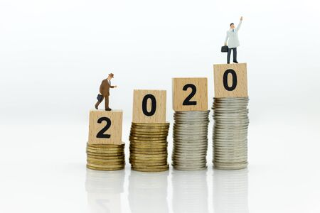 Miniature people: Businessman standing with stack of coins and wooden block 2020. Image use for investment for benefit of year, business concept. Stock Photo