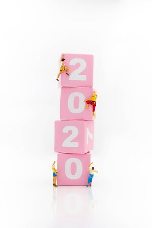 Miniature people: Climbers are climbing 2020 wooden block. Image use for moving forward to success,happy new year concept. Stock Photo