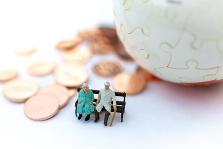Miniature people: Old couple figure sitting on the chair. Image use for background retirement planning, Life insurance concept. Stock Photo