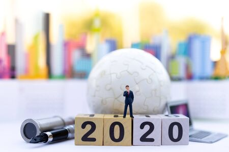 Miniature people : Businessman standing on wooden block new year , with new solution of technology business. Image use for marketing, business concept