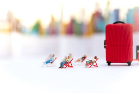Miniature people : Businessman sitting on chair and have a red suitcase, city for background. Image use for travel, business concept.