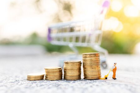 Miniature people: Worker use pallet truckwith stack of coins. Image use for logistic, retail business concept Banque d'images