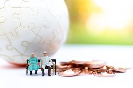 Miniature people: Old couple figure sitting on the chair. Image use for background retirement planning, Life insurance concept. Banque d'images