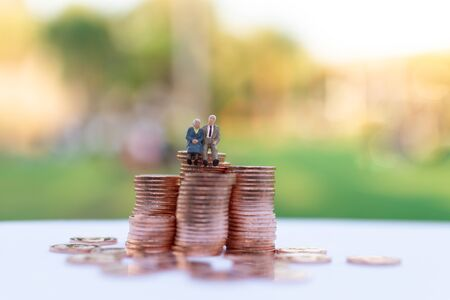 Miniature people: Old couple figure sitting on stack of coins . Image use for background retirement planning, Life insurance concept.