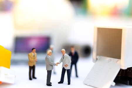 Miniature people : Businessmen shake hands to do business together. Image use for logistic concept, shipment, cargo