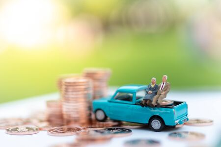 Miniature people: Old couple figure sitting on the car with  stack of coins . Image use for background retirement planning, Life insurance concept