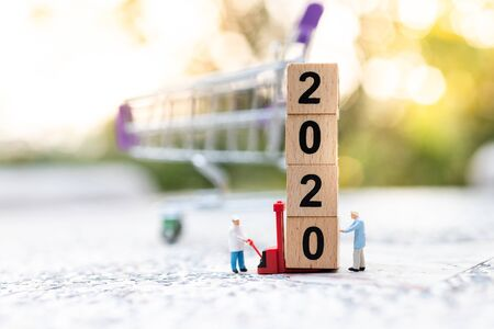 Miniature people: Worker use pallet truck with wooden block  new year . Image use for logistic, retail business concept