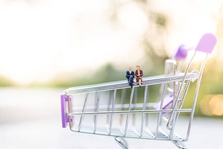 Miniature people : Businessman sitting on shopping cart. Image use for retail business concept.
