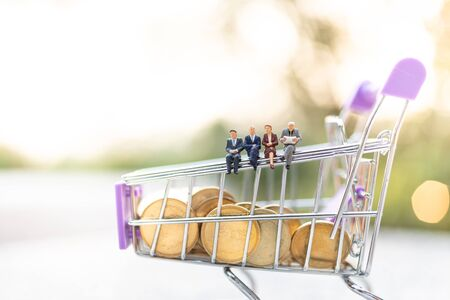 Miniature people : Businessman sitting on shopping cart. Image use for retail business concept. Stock Photo - 143229578