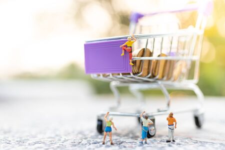 Miniature people : Women are climbing on shopping cart. Image use for retail business concept, shopping concept Banque d'images