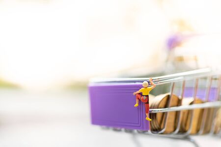 Miniature people : Women are climbing on shopping cart. Image use for retail business concept, shopping concept Stock Photo - 143229587