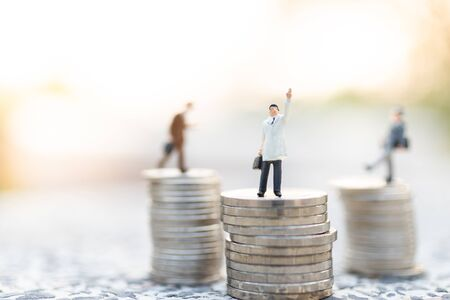 Miniature people : Businessman standing on stack of coin . Image use for business concept. Stock Photo