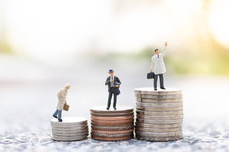 Miniature people : Businessman standing on stack of coin . Image use for business concept. Banque d'images