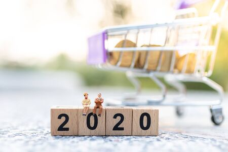 Miniature people: Businessman sitting on wooden block new year . Image use for business concept, new solution for improve business