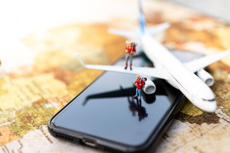 Miniature people: travelers with backpack standing on mobile phone travel by plane and booking ticket online. Image use for travel business concept. Stock Photo - 143229607