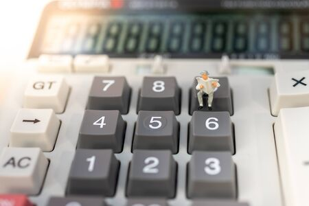 Miniature people: Businessman stand on calculator, tax, profit margins of  background. Image use for business concept.