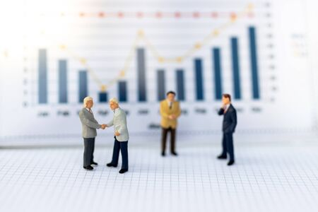 Miniature people : Businessmen earn profits from work, reference the graph to increase benefit. Image use for as a business concept. Stock Photo
