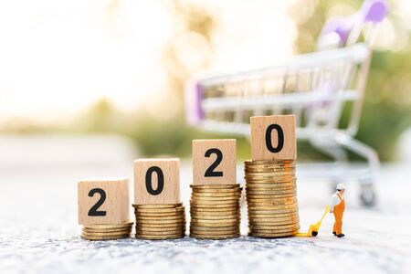 Miniature people: Worker use pallet truckwith stack of coins and wooden block  new year. Image use for logistic, retail business concept Stock Photo - 144198100